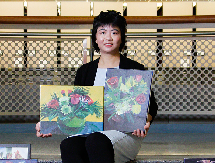 indoor photo of art student Dan Li sitting on the library steps with her paintings displayed around her
