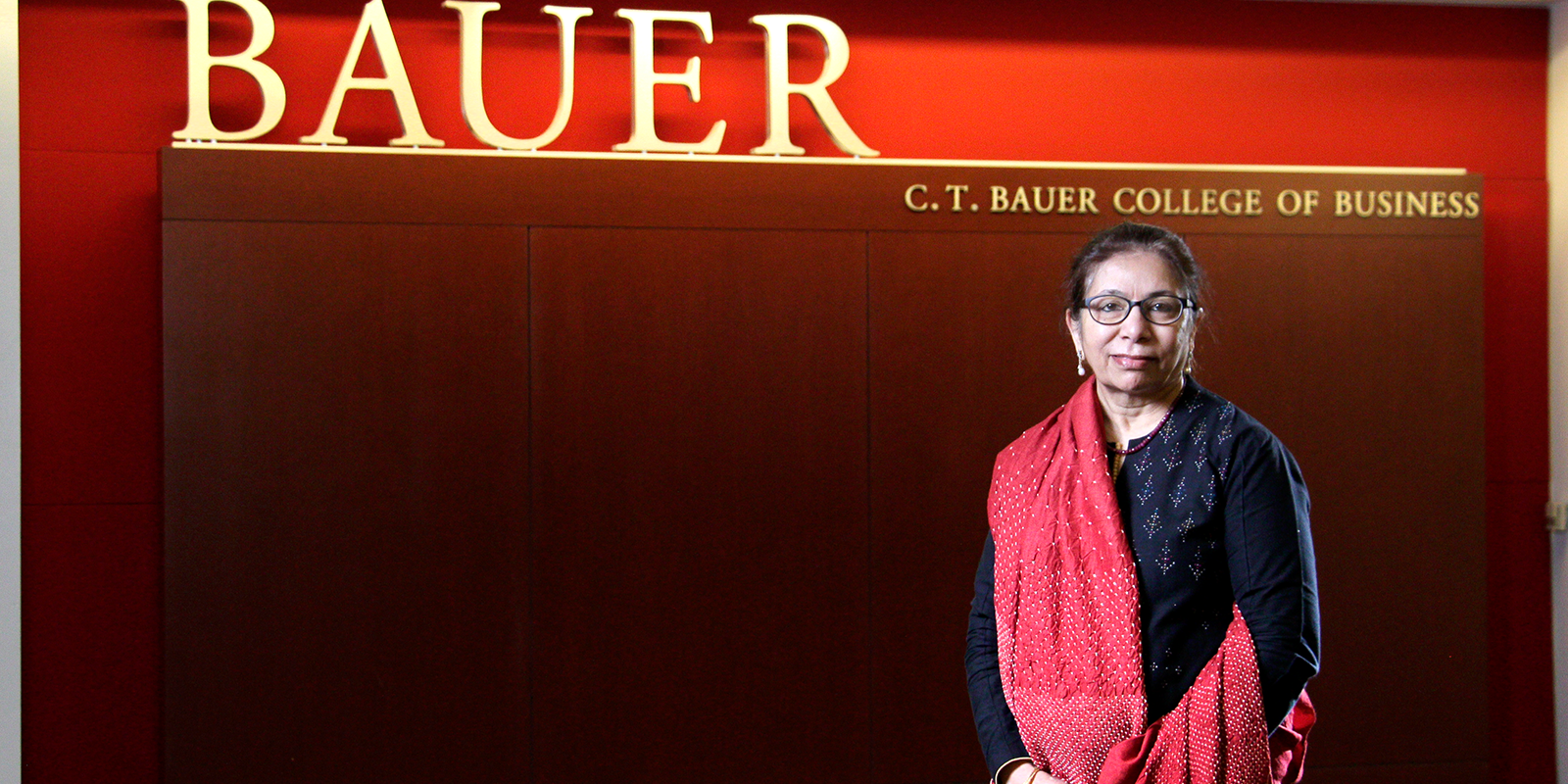 Dr. Khumawala standing in from an interior Bauer College of Business sign