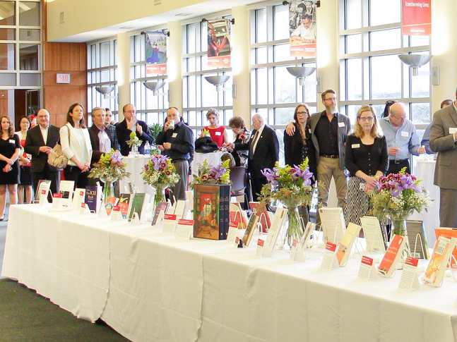 large number of guests standing around a table that is displaying books