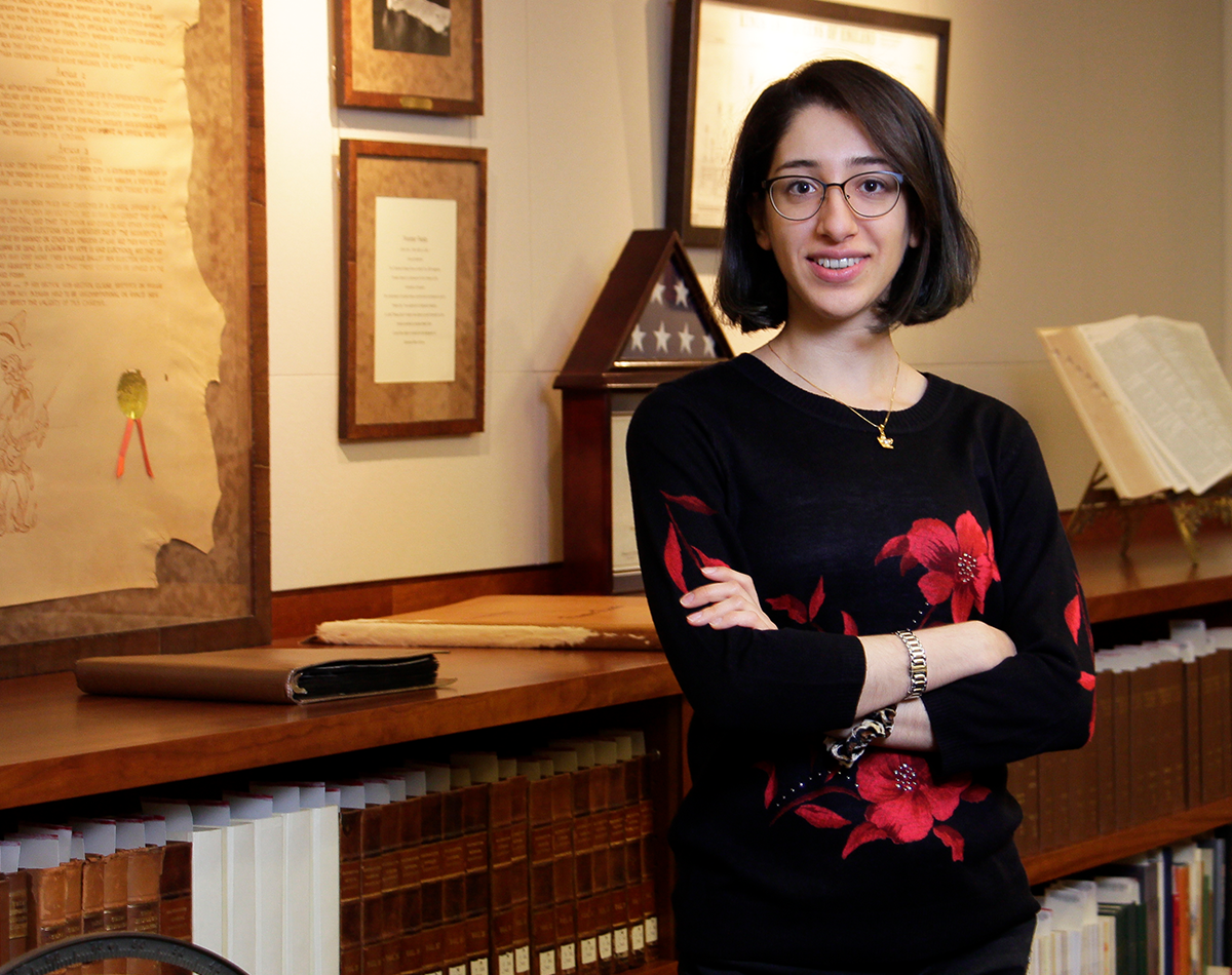 Sara Nafaryeh standing next to bookshelf in Special Collections Reading Room