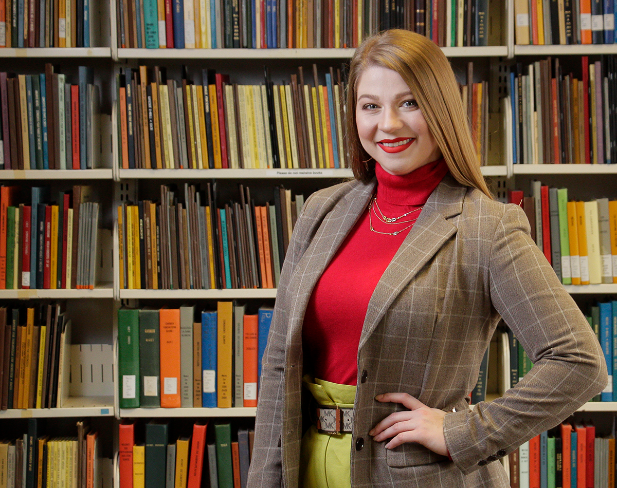 Krista Renée Pape standing in front of bookshelf in Music Library