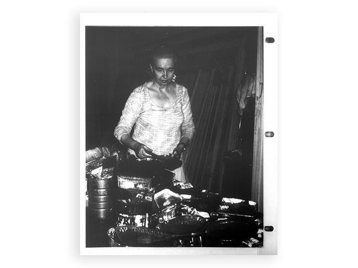 scan of a black and white photo of a woman standing next to pots and pans