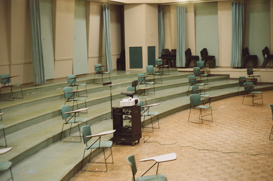 photo of an empty lecture hall with sparse desks socially distanced