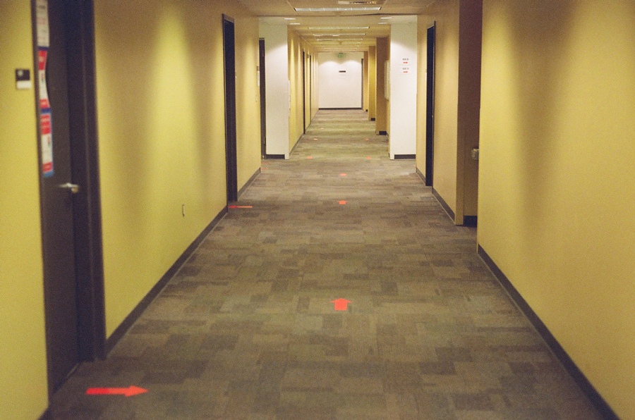 photo of an empty hallway with arrows taped to carpet to direct socially distanced traffic