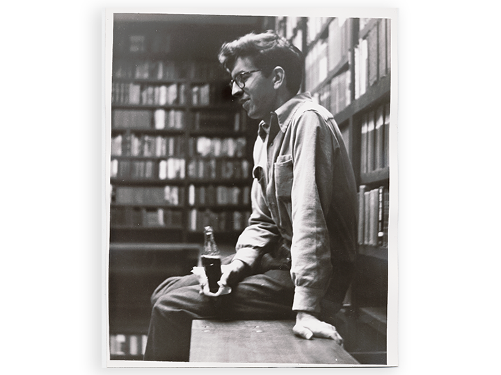 black and white photo of a young Larry McMurtry sitting on a desk drink a Coca-Cola from a glass bottle