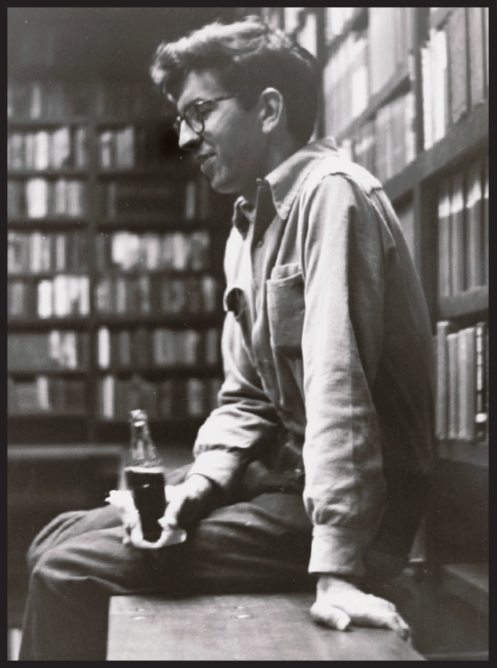 black an white photo of a young Larry McMurtry sitting on a desk drink a Coca-Cola from a glass bottle