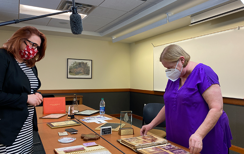 photo of Nancy Sims displaying artifacts to Polina Kharmats on Reading Room table in U.H. Special Collections
