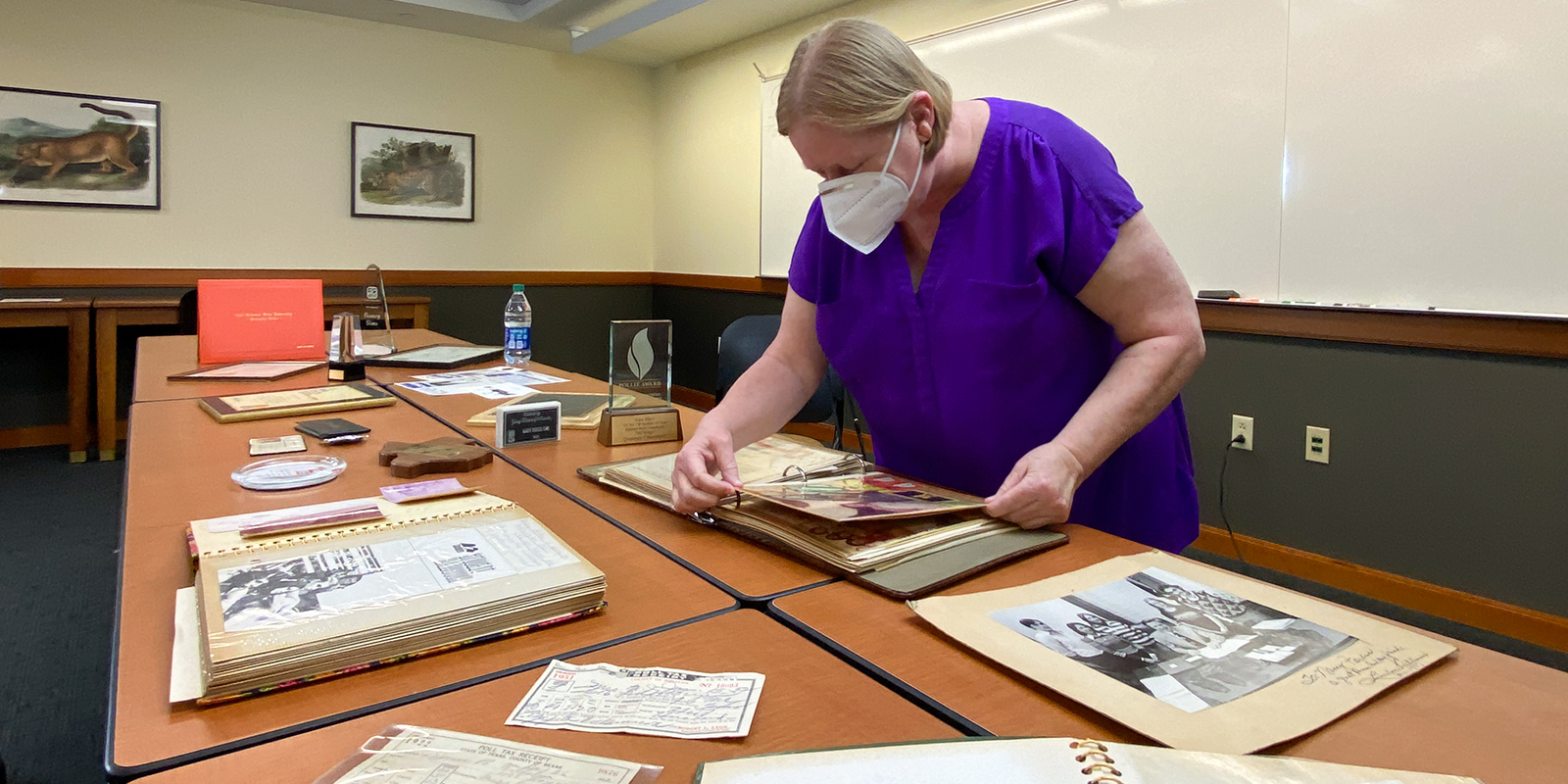 picture of Nancy Sims browsing artifacts on a table in the Special Collections Reading Room