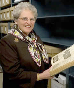 Image of Carey Shuart looking at a book in the Special Collections vault