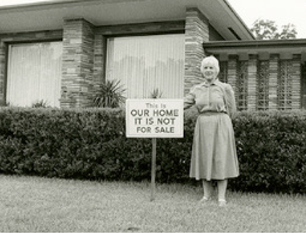 A woman standing in a yard next to a sign that reads This Is Our Home, It Is Not For Sale
