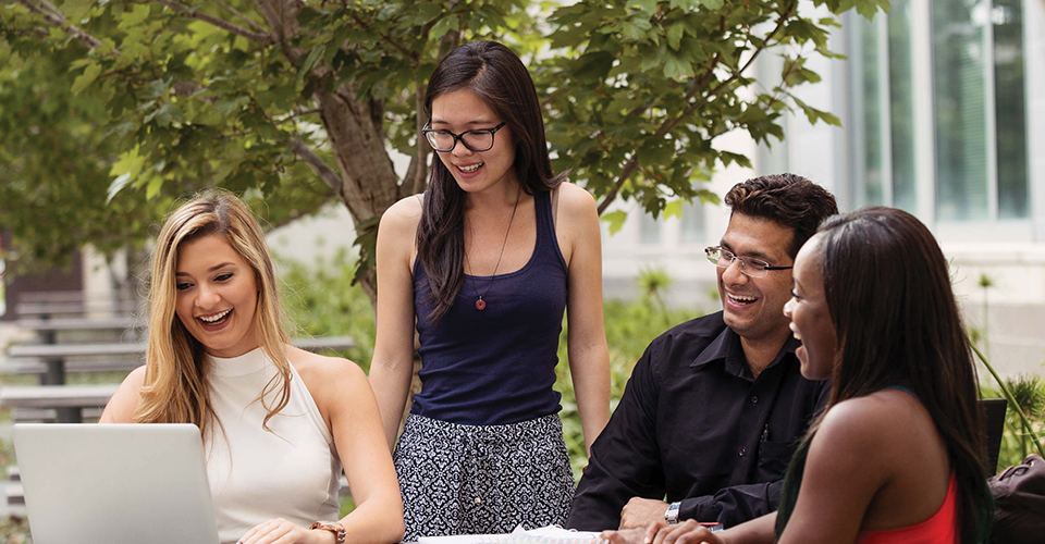 group of students collaborating at an outdoor table