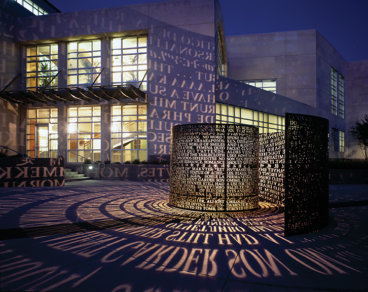 image at night of the front of MD Anderson library with the A,A sculpture lit up