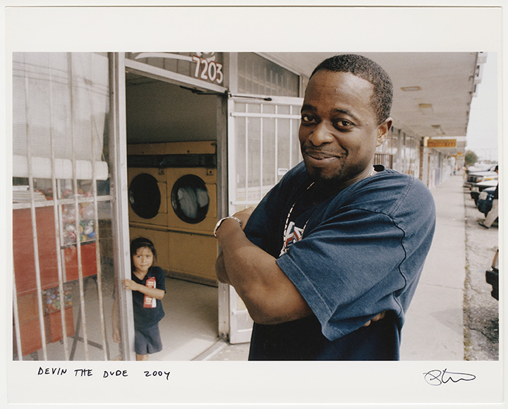 Devin the Dude posing outside of a laundromat